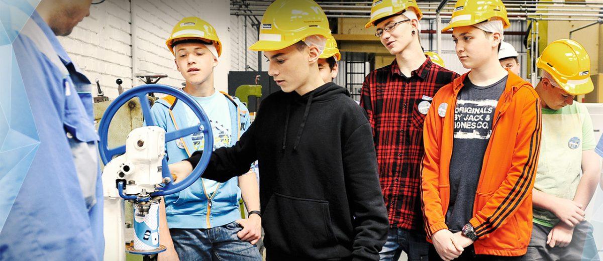 Jugendliche mit Bauhelmen begutachten die Dosenherstellung beim Tag der Verpackung