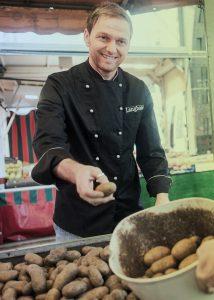 Koch auf dem Markt mit Kartoffeln