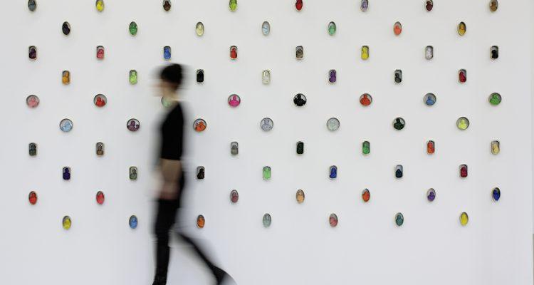 Frau geht an Wand mit Dosenkunst vorbei