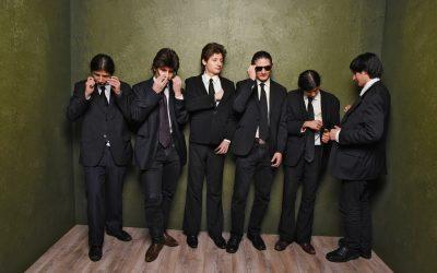 Sechs Männer mit schwarzen Anzügen, Krawatten und Sonnenbrillen bilden das Wolfpack