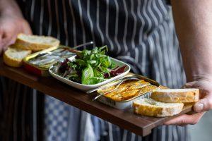 Dosenfisch, Salat und Baguette serviert auf einem Holzbrett: Szene-Gastronomie in Deutschland