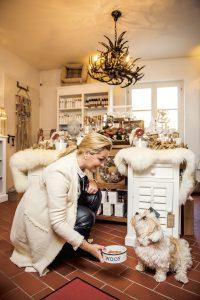 Frau füttert Hund in Geschäft